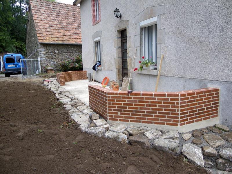 Préparation d'un support avec muret en briques rouges pour réception d'une véranda.