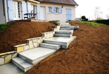 Escalier d'accès en béton armé avec paliers de repos successif afin d'épouser la forme du talus.